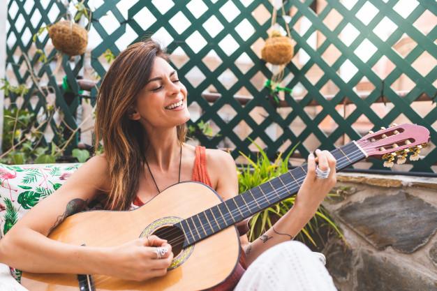 hermosa-mujer-tocando-guitarra-al-aire-libre_102573-441